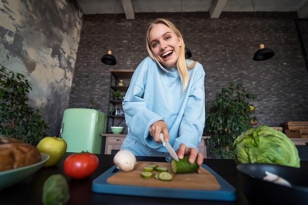 Piękna kobieta opowiada na telefonie komórkowym w kuchni w domu