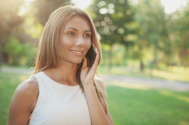 Piękna kobieta opowiada na telefonie outdoors