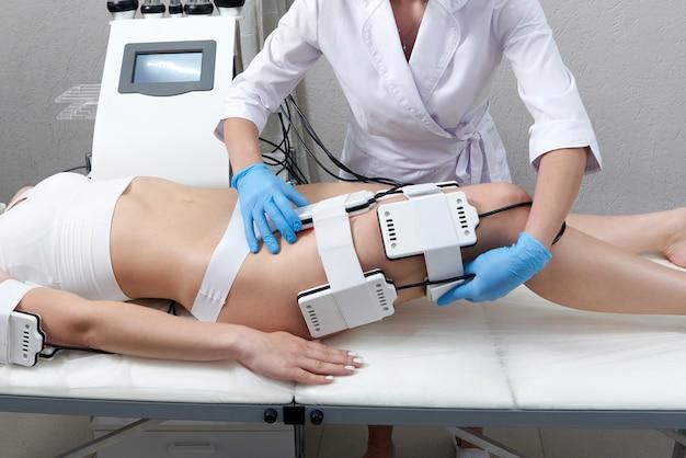 Piękna kobieta otrzymuje laserową terapię elektrostymulacyjną sprzęt lipo kosmetyczną redukcję tłuszczu