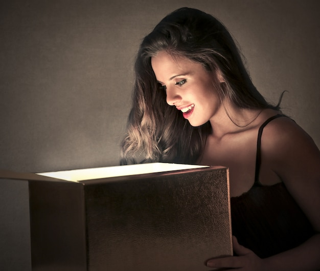 Piękna kobieta otwiera pudełko