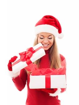 Piękna kobieta, otwierając prezent na boże narodzenie