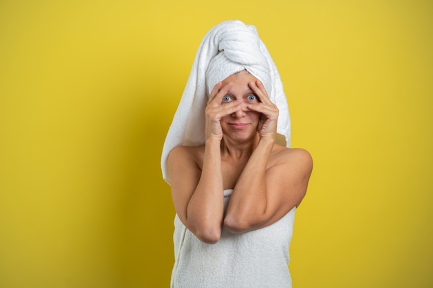 Piękna kobieta owinięta w ręcznik pokazuje różne emocje rękoma na żółtym tle