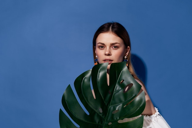 Piękna kobieta palmy zielony liść egzotyczny podróżował niebieskim tle.