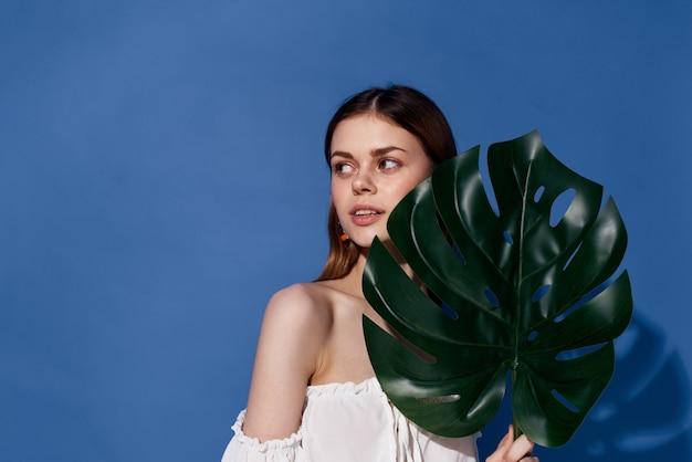 Piękna kobieta palmy zielony liść egzotyczny podróżował niebieskim tle