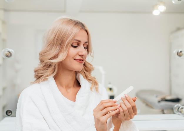 Piękna kobieta, patrząc na jej zdrowy manicure