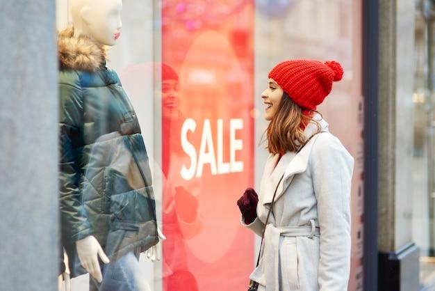 Piękna kobieta, patrząc na okno sklepu podczas zakupów
