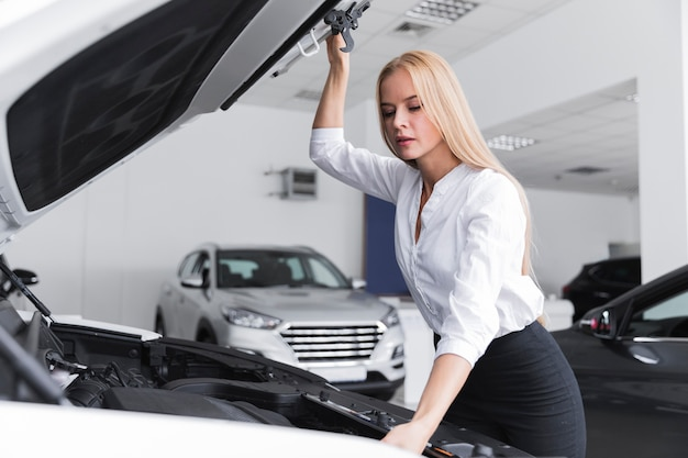 Piękna kobieta, patrząc pod maską samochodu