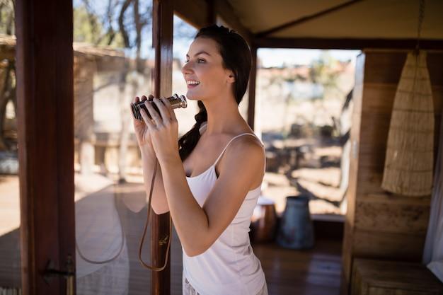 Piękna kobieta patrzeje przez lornetek od okno