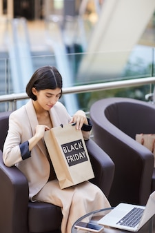 Piękna kobieta patrzeje w torba na zakupy