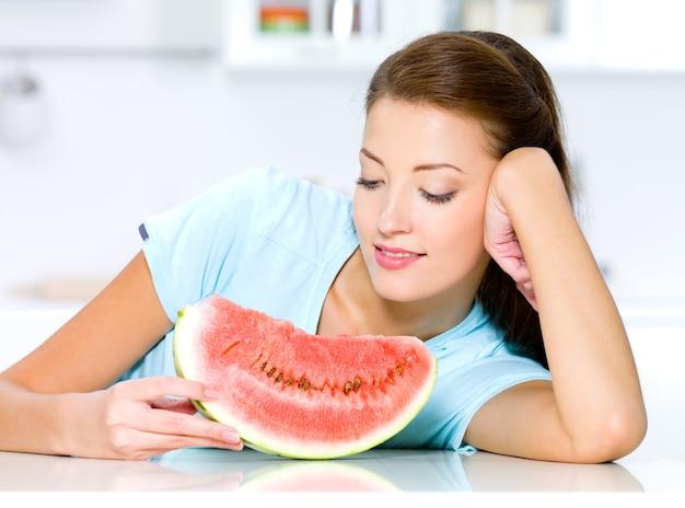 Piękna kobieta patrzy na czerwony arbuz w kuchni