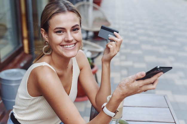 Piękna kobieta patrzy w kamerę i płaci za zakupy kartą i telefonem.