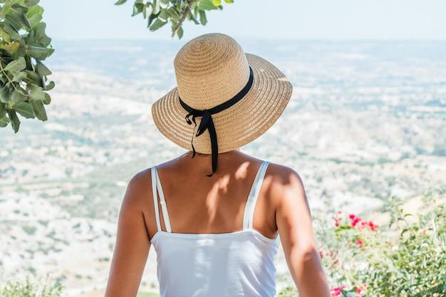 Piękna kobieta patrzy w słomkowy kapelusz