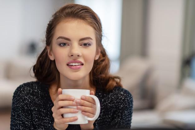 Piękna kobieta picia kawy rano w domu