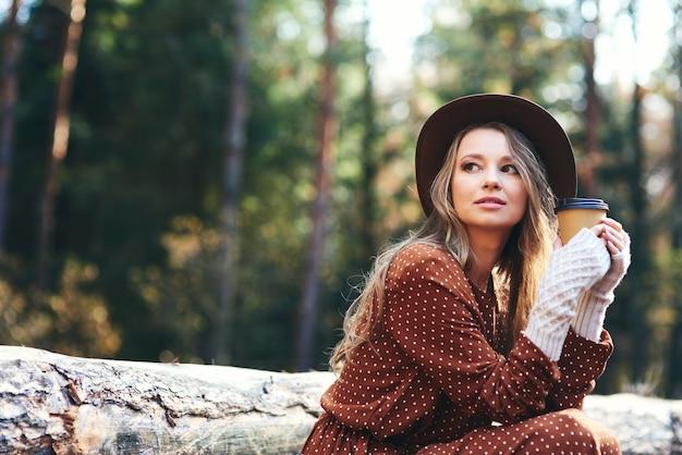 Piękna kobieta pije gorącą kawę w jesiennym lesie