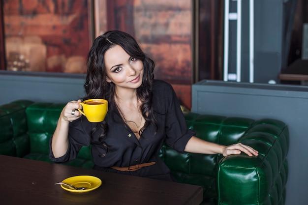Piękna kobieta pije gorący napój. szczęśliwy i wesoły model z jasną filiżanką kawy
