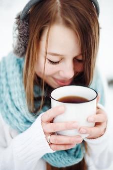 Piękna kobieta pije gorący napój w winter park. koncepcja ferii zimowych. strzał w głowę z bliska. selektywna ostrość.