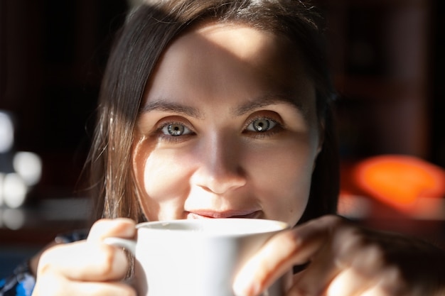 Piękna kobieta pije kawę w ranku przy kawiarnią.
