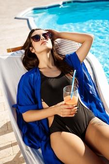 Piękna kobieta pije koktajl, kłama na bryczce blisko pływackiego basenu