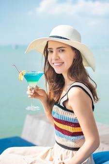 Piękna kobieta pije lodowego lato napój w plaży, lata pojęcie