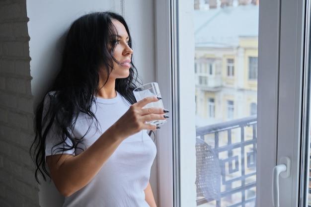 Piękna kobieta pije napój mleczny, yougurt ze szkła