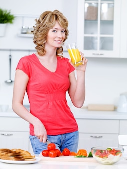 Piękna kobieta pije sok pomarańczowy i gotuje w kuchni - w pomieszczeniu