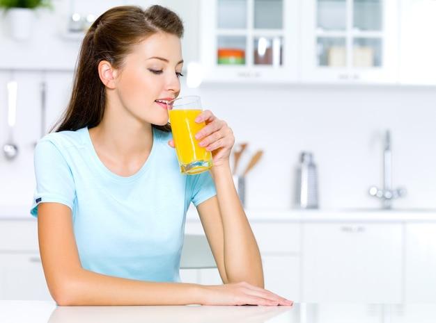 Piękna kobieta pije świeży sok pomarańczowy