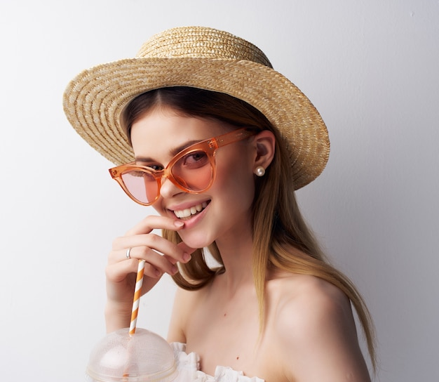 Piękna kobieta pije ze słomkowym jasnym tłem