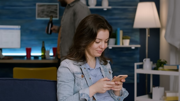 Piękna kobieta pisania wiadomości na e-mail za pomocą telefonu siedzi na kanapie późno w nocy w salonie. w tle jej wieloetniczne przyjaciółki pijące piwo, bawiące się podczas weekendowej imprezy