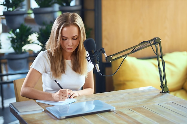 Piękna kobieta pisze informacje w zeszycie