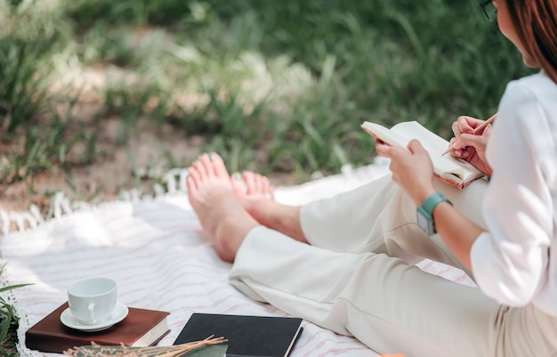 Piękna kobieta pisze na pamiętniku w parku.