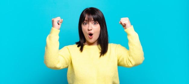 Piękna kobieta plus size świętująca niewiarygodny sukces jak zwycięzca, wyglądająca na podekscytowaną i szczęśliwą, mówiąc: weź to!