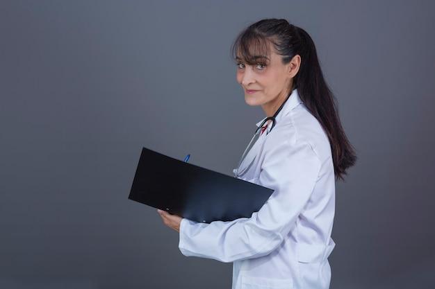 Piękna kobieta po czterdziestce z folderem z długimi włosami w dłoni zwróconej w stronę aparatu