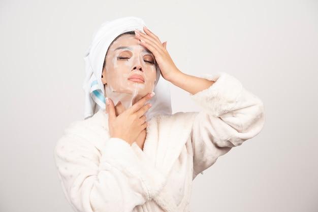 Piękna kobieta po prysznic z ręcznikiem na głowie.