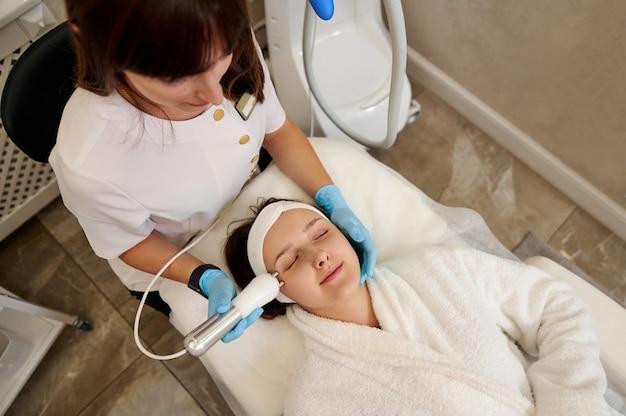 Piękna kobieta po zabiegu mikroprądu twarzy od kosmetyczki w gabinecie odnowy biologicznej. terapia mikroprądowa.
