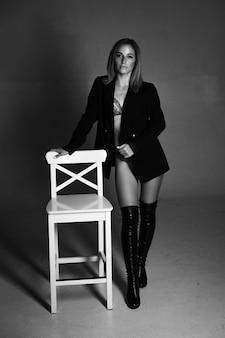 Piękna kobieta pochodzenia kaukaskiego pozuje siedząc na krześle w czarnej kurtce i bieliźnie