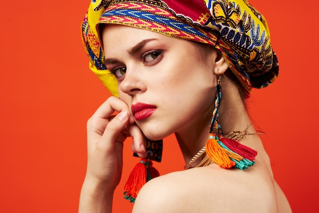Piękna kobieta pochodzenie etniczne wielobarwny chustka na głowę makijaż glamour czerwone tło