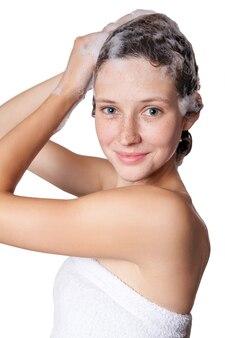 Piękna kobieta pod prysznicem i szamponem włosy. mycie włosów szamponem. studio strzał na białym tle.
