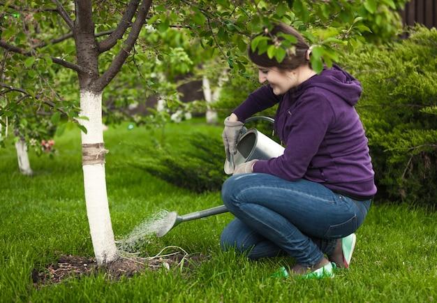 Piękna kobieta podlewa drzewo w ogrodzie z konewką
