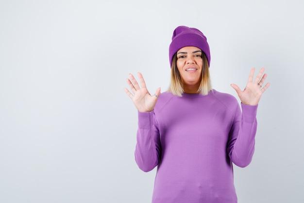 Piękna kobieta podnosząc ręce w geście kapitulacji w sweter, czapka i bezradna. przedni widok.
