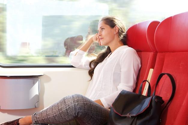 Piękna kobieta podróżuje pociągiem przyglądającym out okno
