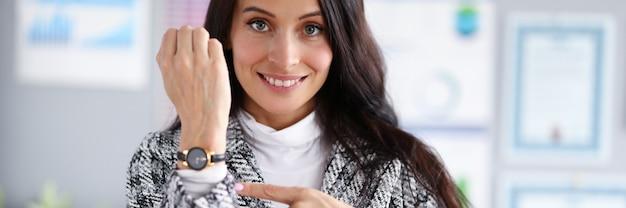 Piękna kobieta pokaż palec na dłoni z zegarem