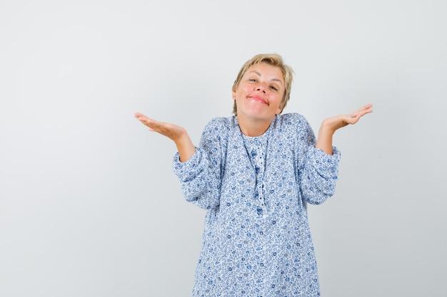 Piękna kobieta pokazując idk gest we wzorzystej bluzce i patrząc leniwy. przedni widok.