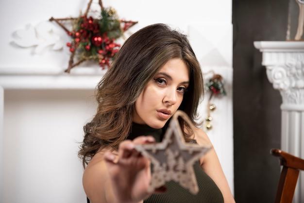 Piękna kobieta pokazująca drewnianą gwiazdę do kamery w salonie