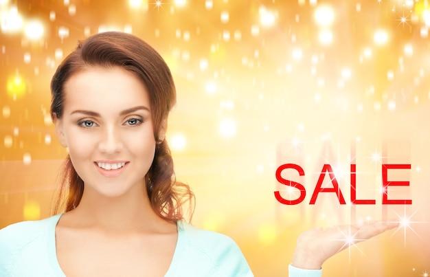 Piękna kobieta pokazująca słowo sprzedaż na dłoni