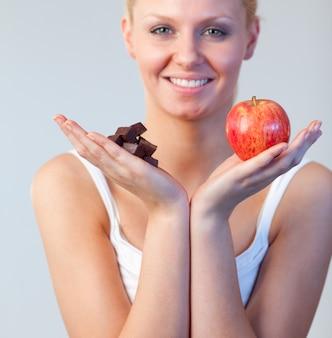 Piękna kobieta pokazuje czekoladę i jabłko i patrzeje kamerę skupiamy się na czekoladzie i jabłku