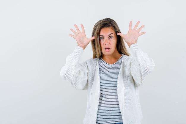 Piękna kobieta pokazuje dziesięć palców w kurtce i patrzy na jawie. przedni widok.