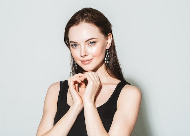 Piękna kobieta portret z fryzurą idealny makijaż. biżuteria modelka. szare tło.