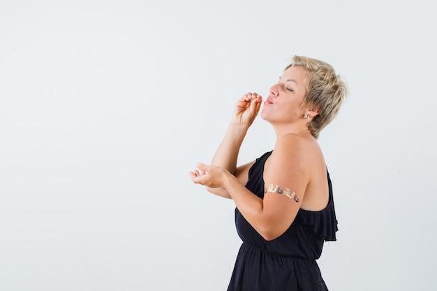 Piękna kobieta pozuje jak picie w czarnej bluzce i wygląda spokojnie