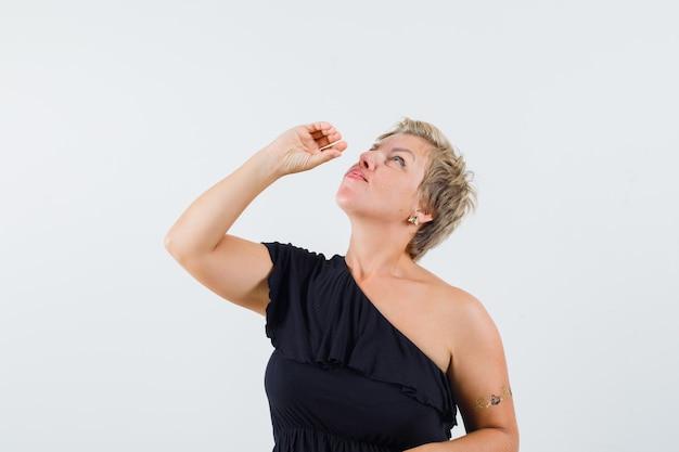 Piękna kobieta pozuje jak picie w czarnej bluzce