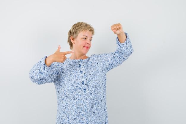 Piękna kobieta pozuje jak podniesienie czegoś, wskazując na to we wzorzystej bluzce i patrząc skupiona. przedni widok.
